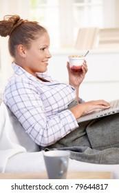 Pretty girl browsing Internet in bed, using laptop, smiling, eating yoghurt.?