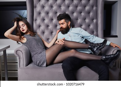 Pretty girl with brunette curly hair, red lipstick and handsome cute bearded man. Fashion photo of beauty salon romance of sexy lovers. Beautiful fashion couple in love. Concept of Valentines day.