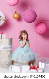 Pretty girl child 4 years old in a blue dress. Baby in Rose quartz room decorated holiday.