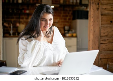 Pretty girl with chubby cheeks sitting at table in front of open laptop using earphones studying online. Cute young woman in plus size white blouse watching webinar online, having curious look