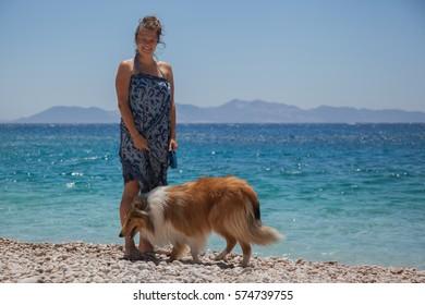 Pretty girl with collie dog on mediterranean summer beach