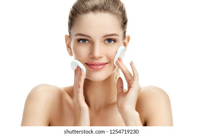 Pretty girl with cotton pads cleans her face on white background. Skin care and beauty concept.