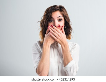 Pretty girl covering her mouth over grey background