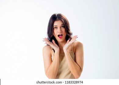 Pretty girl in cream costume shows a surprised look to the thrill of open mouth and eyes before the miraculous Isolated on white background.