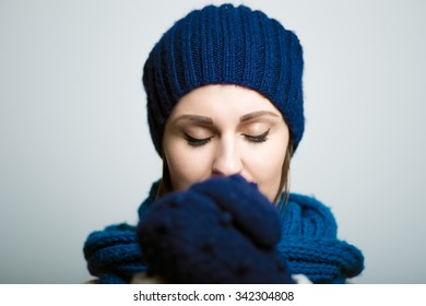 Pretty girl crossed her arms, dressed in winter clothes, bright lifestyle photo, isolated on a gray background