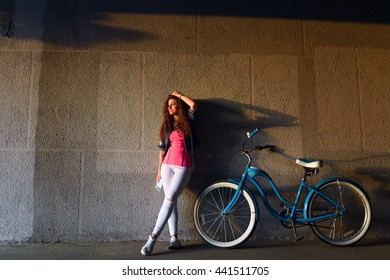 Pretty girl with curly hair is resting at sunset with his bike