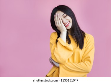 Pretty girl cute laughs in a frame on a pink background. Laughter, joy, mercy, youth, good joke, emotional reaction, hand covers the face, funny and friendly, sincerity