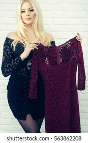 pretty girl or cute woman with long platinum blonde hair and fashionable makeup on face in sexy black skirt and blouse holds lace purple dress on white brick wall background in wardrobe or showroom