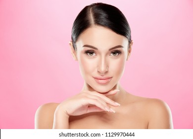 Pretty girl with dark hair, big eyes, dark eyebrows and shoulders looking at camera, a model with light  make-up, beauty photo, at pink background.
