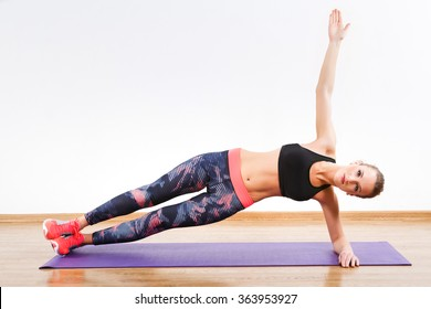 Pretty girl with dark hair wearing pink snickers, dark leggings and black short top doing side plank on one hand at gym, fitness, white wall and wooden floor.