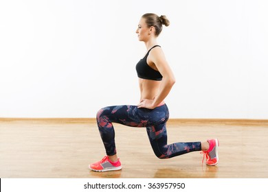 Pretty girl with dark hair wearing pink snickers, dark leggings and black short top doing lunge at gym, fitness, white wall and wooden floor, copy space.