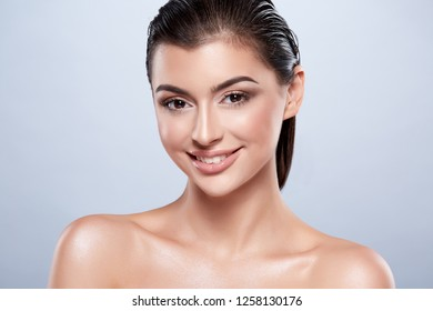 Pretty girl with dark wet hair and nude make up and naked shoulders at studio background, skin care concept, portrait.