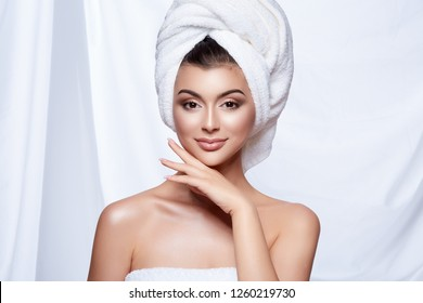 Pretty girl with dark wet hair and nude make up wearing white towel at white studio background, beauty photo, SPA concept.