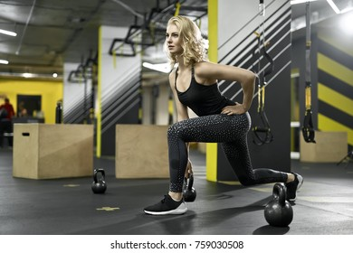 Pretty girl does squats with the weight in the gym. She wears dark pants with same sleeveless and black sneakers. Woman holds left hand on the hip and looks forward with parted lips. Horizontal.