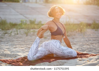 Pretty girl doing yoga exercises outdoor.Young white woman in good mood stretching on beach at sunset.Attractive athlete stretches on blanket before workout.Wellness and female health concept