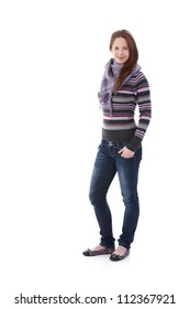 Pretty girl dressed for autumn, standing with hands in pocket, smiling at camera.
