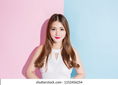 pretty girl  dressed in white dress  standing with arms akimbo isolated on a pink and blue background.