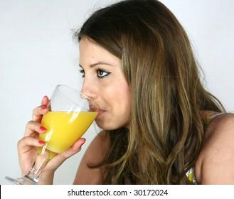 A pretty girl drinks a glass of orange juice