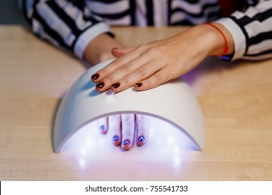 pretty girl dry your nails in the UV lamp