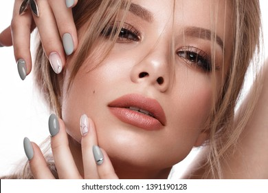 Pretty girl with easy hairstyle, classic makeup, nude lips and manicure design. Beauty face. Art nails. Studio portrait