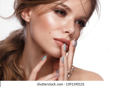 Pretty girl with easy hairstyle, classic makeup, nude lips and manicure design with jar of nail polish in her hands. Beauty face. Art nails. Studio portrait
