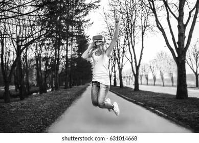 Pretty girl enjoy virtual reality glasses, black and white
