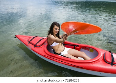 pretty girl exercising in a red kayak on a lake.