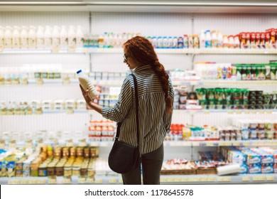 Pretty girl in eyeglasses and striped shirt choosing milk in dairy department in modern supermarket