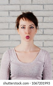 A pretty girl with face mimic for phonetic exercise, her mouth squeezed in a small circle, white brick wall in the background