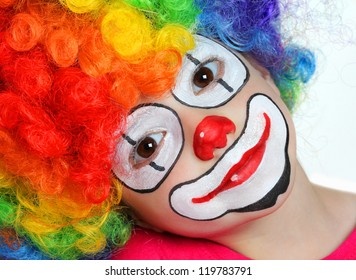Pretty girl with face painting of a clown