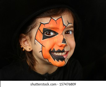 Pretty girl with face painting of a pumpkin isolated on black background