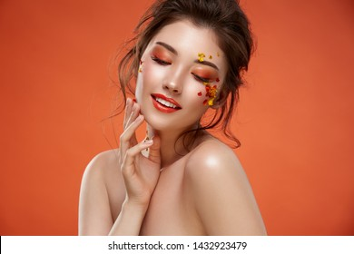 pretty girl with fashion make-up and flowers on her face on orange background, beautiful woman spring look, sensetivy beauty