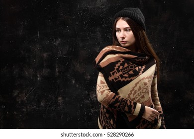 Pretty girl in fashionable clothes on a black background textured wall