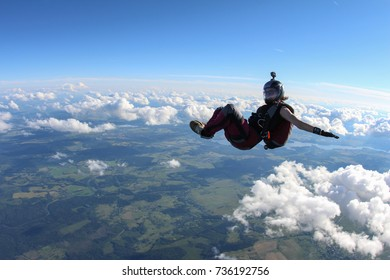 Pretty girl is flying above white clouds.