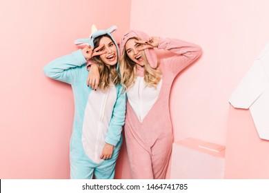 Pretty girl in funny kigurumi laughing with friend. Wonderful european ladies posing in cute pajamas.