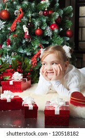 Pretty girl with gifts lying and smiling near christmas tree