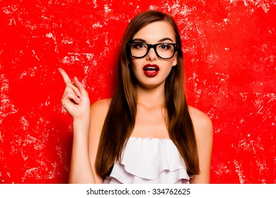 Pretty girl with glasses pointing away against the red background
