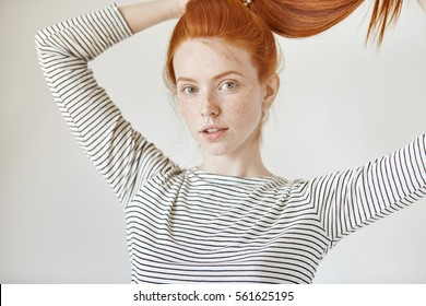 Pretty girl with green eyes and freckles smiling joyfully tying her long red hair in ponytail, getting ready before going out to cinema with friends. Young Caucasian female model posing in studio