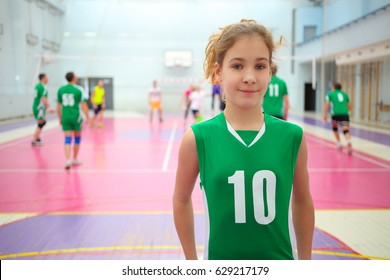Pretty girl in green smiles in gym during volleyball game, playing people out of focus
