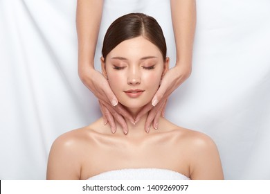 pretty girl having massage for her neck lying on white, body treatment and spa theraphy for female, beautician working on woman's body