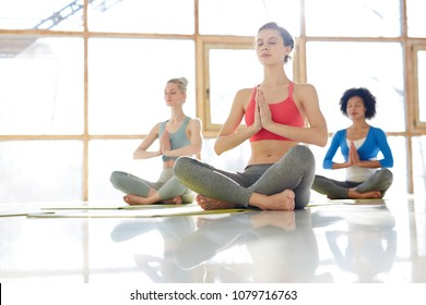 Pretty girl and her groupmates in activewear sitting on mats in one of yoga postures and relaxing