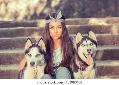 Pretty girl and her pets. Swag rapper woman with her husky dogs isolated urban grey wall background sitting on stairs all three looking at you cameraTaking dog out. The man's women best friend concept