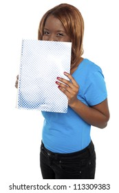 Pretty girl hiding her face through notebook. Casual young college student