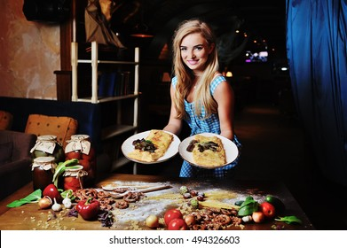 pretty girl holding a cake covered with cheese on the table with food background