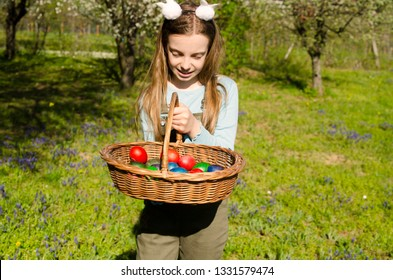 Pretty girl holding Easter colorful eggs in wicker basket outdoor in green grass.Happy child on spring holiday with basket ful of Easter eggs