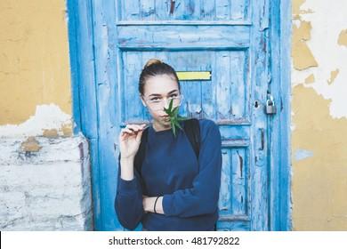 Pretty girl holding a marijuana leaf, standing around old door, posing.