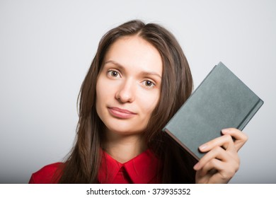 pretty girl holding a notebook for notes on a gray background