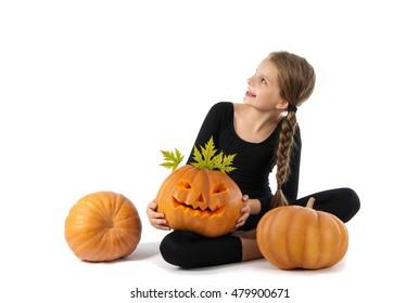 Pretty girl holding a pumpkin. Halloween. The girl smiles. Joy, emotion, holiday.