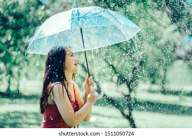 Pretty girl holding umbrella while walking in the park, Asian woman under an umbrella in the rain
