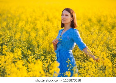 Pretty girl holding yellow flower. Young attractive woman in blue dress standing in yellow field. Allergy free theme. Healthy lifestyle background. Vacation concept. Day off outdoors.